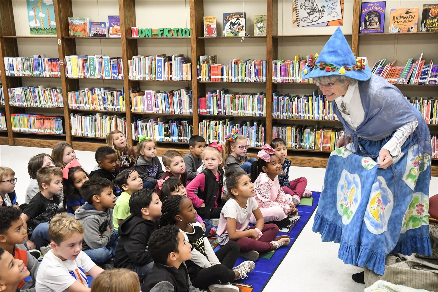 Mother Goose showing her nursery rhyme skirt to students.