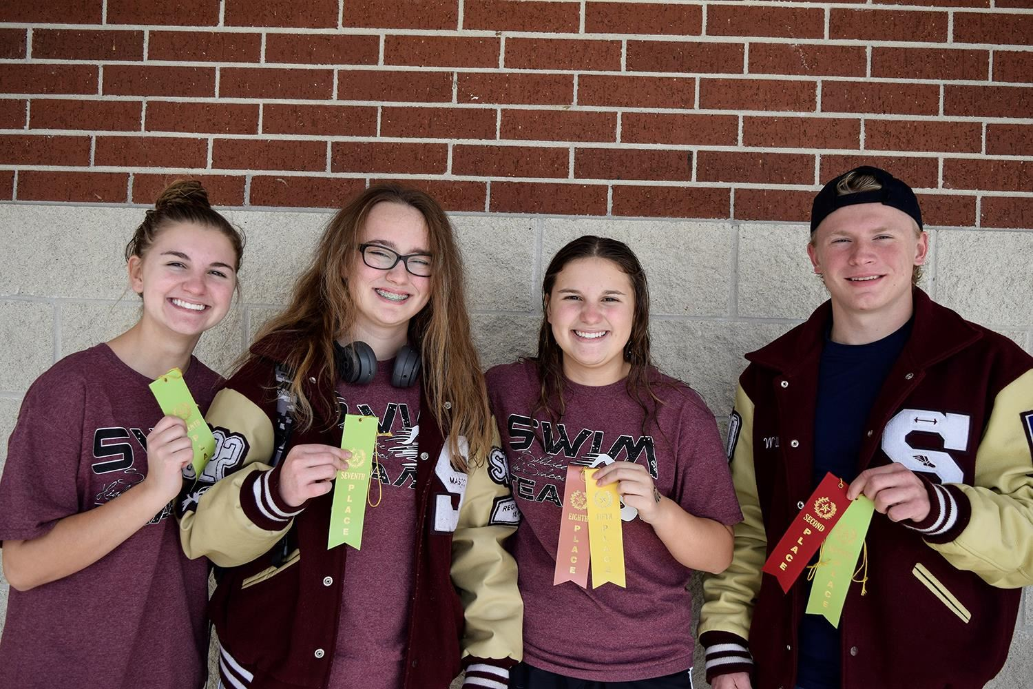 Swim team with winning ribbons.
