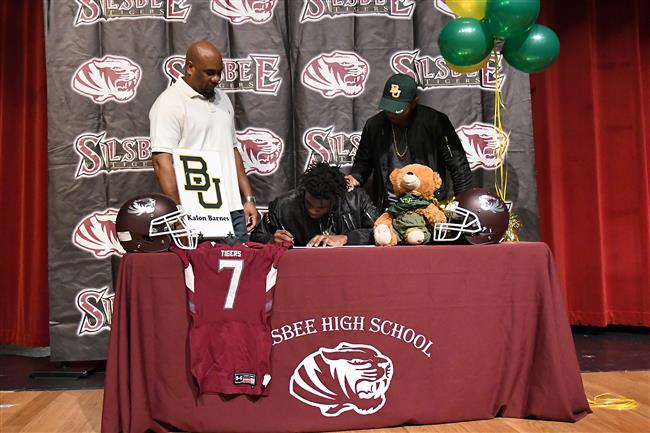 Photo of Kalon Barnes signing letter of intent