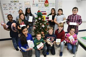 Photo of fourth grade elementary students posing with gifts collected for nursing home patients