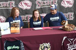 Hannah McInnis poses with her parents after signing