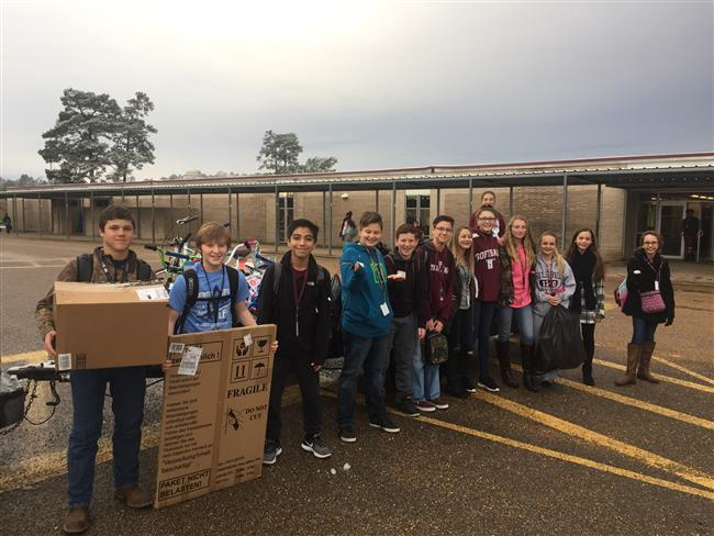 Middle School students pose for a picture during the collection of gifts outside.