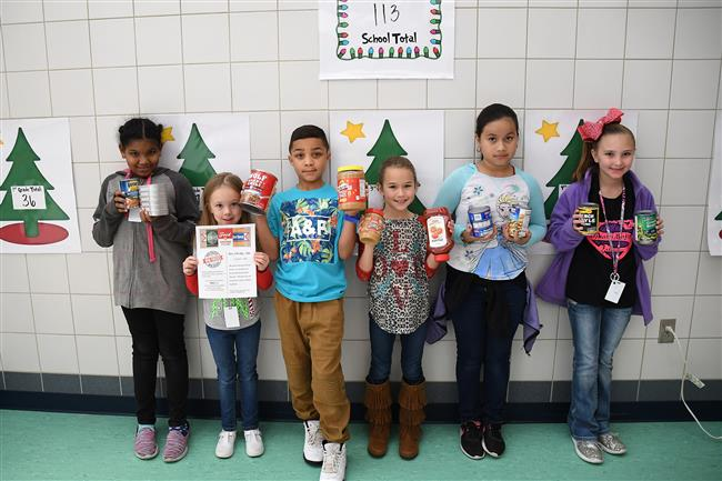 Photo of elementary students holding cans