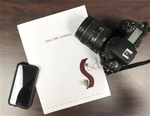 Photo of cell phone, camera and Silsbee ISD marketing folder